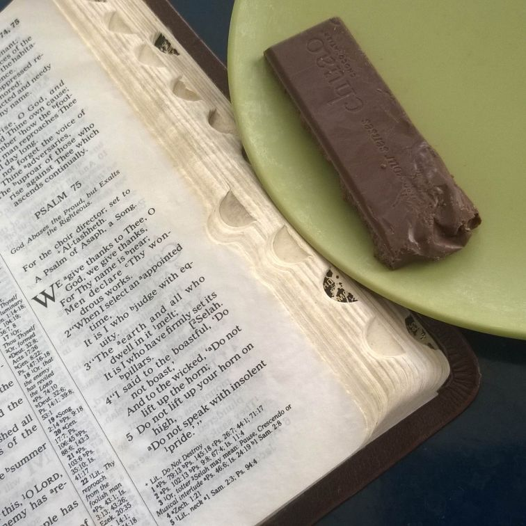 Bible opened to Psalm 75 with Chuao Baconluxious Chocolate on green plate